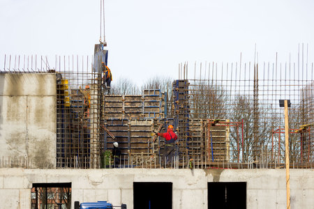 the worker and the crane operator unload the car with reinforced concrete walls for building a large wellness center with a swimming pool of modern technology with concrete poured reinforced and formwork walls. reportage. Stock Photo