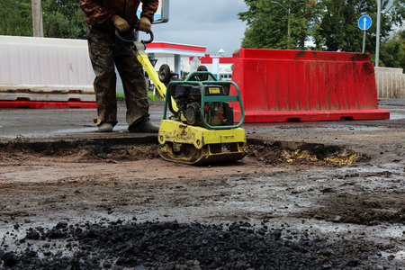 The foreman of the construction team works with a vibrating platform plate, tamping up the sand before the asphalting of the road using the patch method. reportage Stock Photo