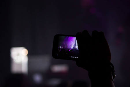 Man hand with a smartphone records a live concert of the group consisting of four cellists and a drummer. The scene is lit with purple spotlights.