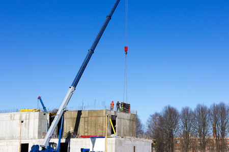 the worker and the crane operator unload the car with reinforced concrete walls for building a large wellness center with a swimming pool of modern technology with concrete poured reinforced.