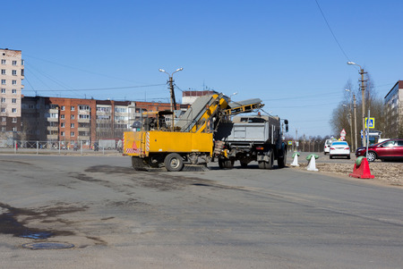 urban sweeper with yellow trailer cleans road from dirt with a round brush in the spring at the crossroads of five roads. Gatchina, Russia, reportage Reklamní fotografie
