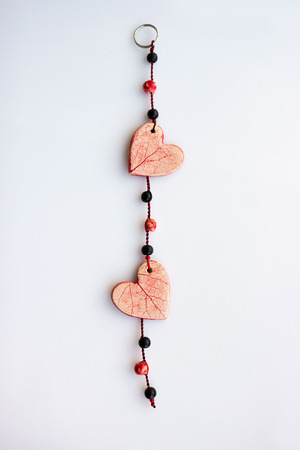 decorative pendant of two hearts. ceramics, red glaze. double kiln firing.