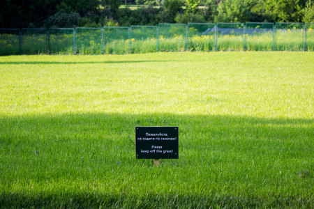 warning label on the meadow Gatchina park. Inscriptions in Russian and English: please do not walk on the lawns.