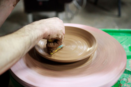 a master ceramist with 13 years of experience makes plate from red clay on a potters wheel, on a sheet of particle board for better removal and further drying. removal of excess moisture from the product using a foam sponge. reportage. Stok Fotoğraf