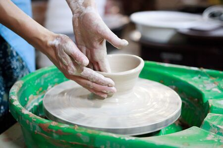 A novice student in the first lesson in pottery tries to make a product from clay on a potters wheel. reportage. Incorrect hand setting