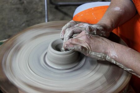 a craftsman with 13 years of experience unscrews a cylinder on a potter's wheel - the fundamental form of any ceramic product.