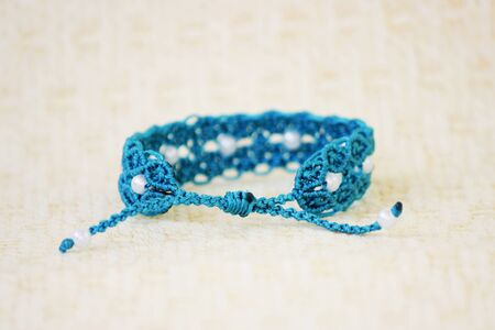 turquoise bracelete with white beads for the hand from waxed thread in the technique of macrame. Handmade.