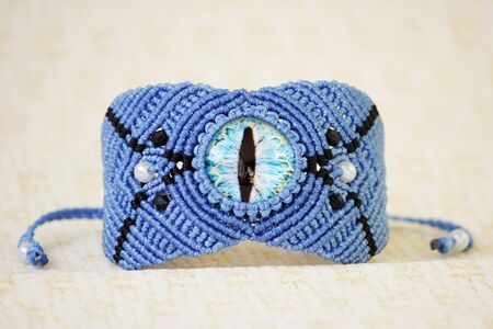 blue bracelete with white beads and the dragons eye on the hand from waxed thread in the technique of macrame. Handmade.