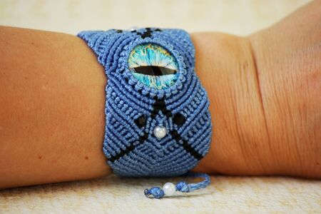 blue bracelete with white beads and the dragons eye on the hand from waxed thread in the technique of macrame. Handmade. put on hand.