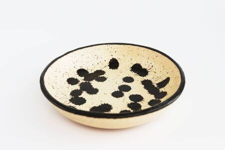 beige clay plate with black spots. made of layer, covered with transparent glaze. two roasting. Handmade ceramics. On a white background Banco de Imagens