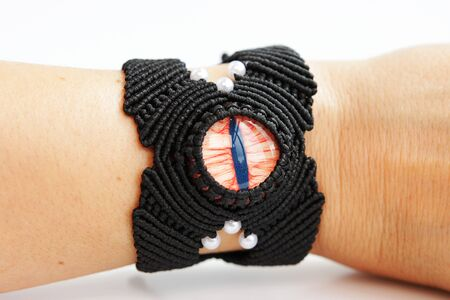 black bracelete with red dragons eye for arm from waxed thread in the technique of macrame on a white background. Handmade. put on hand