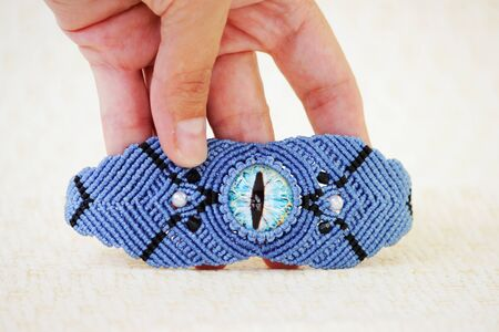 blue bracelete with white beads and the dragons eye on the hand from waxed thread in the technique of macrame. Handmade