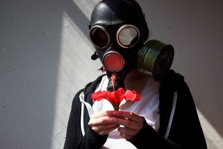 girl in gas mask with a red flower in her hand. cosplay Stock Photo