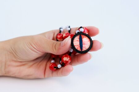 dragon red eye cabochon and ceramic beads in a girl s hand on a white background. Amulet