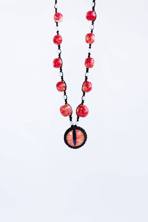 dragon red eye cabochon and ceramic beads on a white background. Amulet