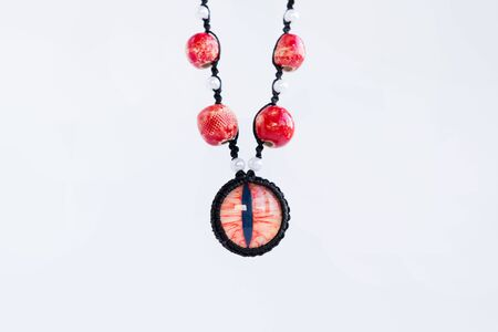 dragon red eye cabochon and ceramic beads on a white background. Amulet Standard-Bild