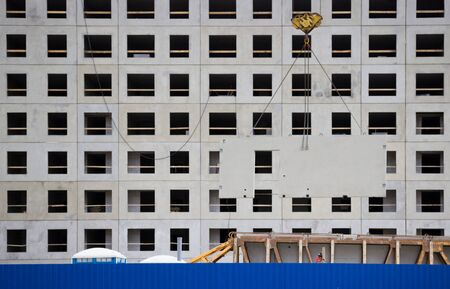 crane unload reinforced concrete walls from the car for the future high-rise building. construction site behind a blue fence. panel house. reportage Banco de Imagens