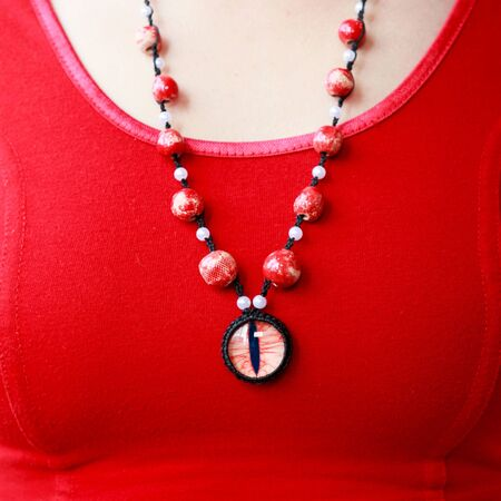 dragon red eye cabochon and ceramic beads. necklace on a young girl on a red background. Amulet Stok Fotoğraf