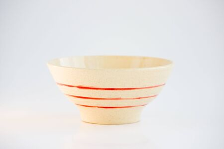 small beige plate with red stripes. handmade. made on a potter s wheel, covered with transparent glaze, burned in a kiln
