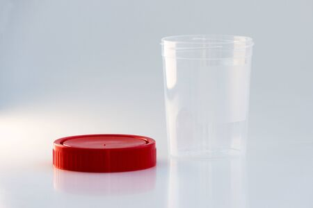 transparent plastic jar with a red lid on a white background. for analysis.