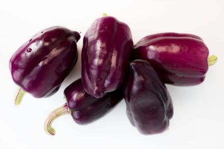 five violet peppers on a white background.