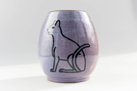 small vase with an Egyptian cat made of red clay covered with transparent glaze. Ancient Egyptian hieroglyph. the glaze turned violet due to excess firing temperature.