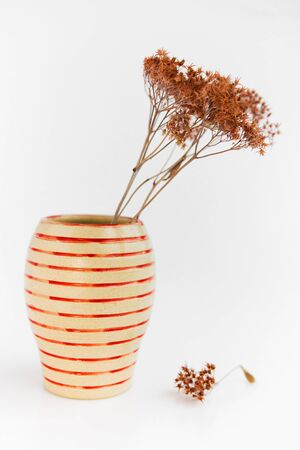 beige clay plate on a white background. minimalism style. handwork and dried flower. vertical photo Stok Fotoğraf