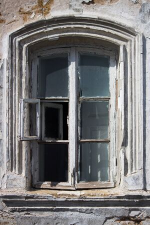 old wooden window with peeling paint in the village. vertical layout
