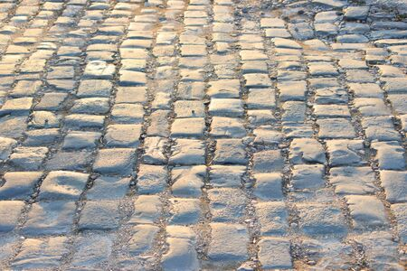 old cobblestone pavement, lit by the rays of the setting sun. golden light.