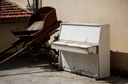 Old white piano and a wagon stand in the open air. Banque d'images