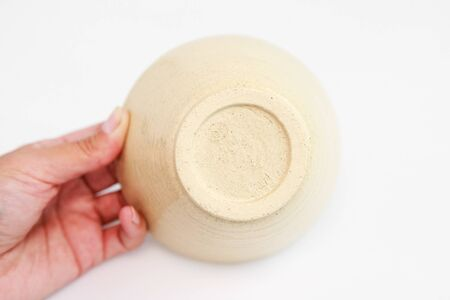 beige clay plate in hand on a white background. minimalism style. handwork