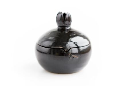 black clay pomegranate on a white background. original casket with a cover in the form of a pomegranate.