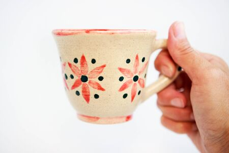 beige clay cup with flowers in hand on a white background. Stok Fotoğraf