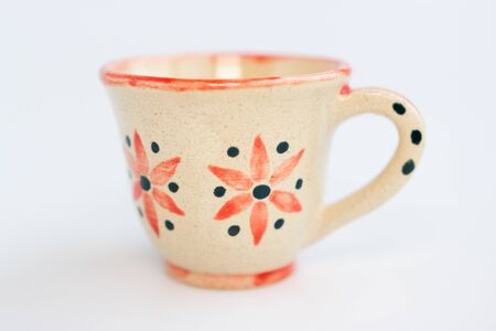 beige clay cup with flowers on a white background.