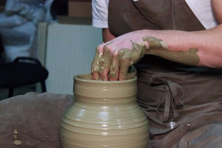 experienced potter makes a large vase on a potter's wheel. clay product. hands of a potter. reportage shooting