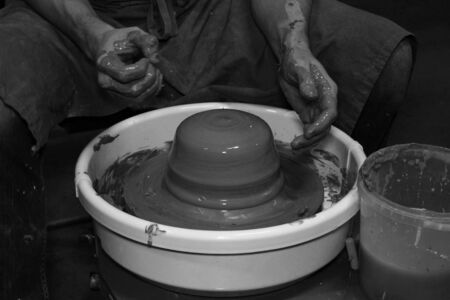 experienced potter makes a large vase on a potter's wheel. twisting a narrow neck. clay product. hands of a potter. reportage shooting. work with a large piece of clay Banque d'images