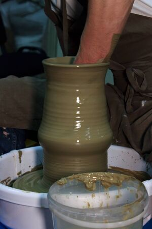 experienced potter makes a large vase on a potters wheel. clay product. hands of a potter. reportage shooting
