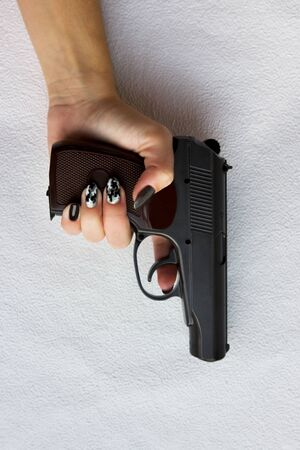 hand of a young woman with a gun on a gray background. vertical.