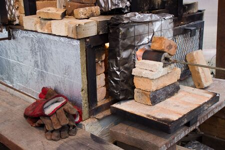 wood firing of ceramic products in a homemade stove. beginning - heating the furnace with a gas burner to remove excess moisture. Banque d'images - 140250776
