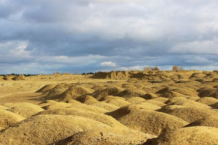 artificial mountains of crushed stone and sand at a quarry for the extraction of building limestone
