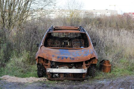 skeleton from a burnt passenger car is in the forest. rusty skeleton, next to the fuel canister Banque d'images