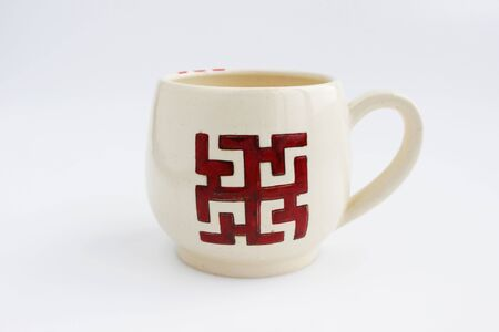ceramic mug with the ancient Slavic sign Dukhobor. Slavic amulet Dukhobor is a symbol aimed at healing from diseases. Banque d'images