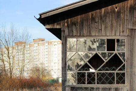old wooden house on the background of a new panel multi-storey building. urban contrasts and combinations Banque d'images - 141503193