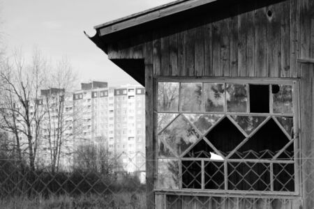 old wooden house on the background of a new panel multi-storey building. urban contrasts and combinations. black and white