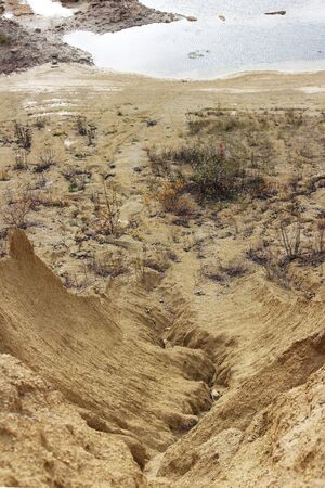 sand quarry. The crack between the two sand dunes is washed out by the rain Standard-Bild - 143462251