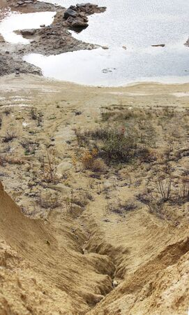 sand quarry. The crack between the two sand dunes is washed out by the rain and an artificial lake nearby. Banque d'images - 141507389