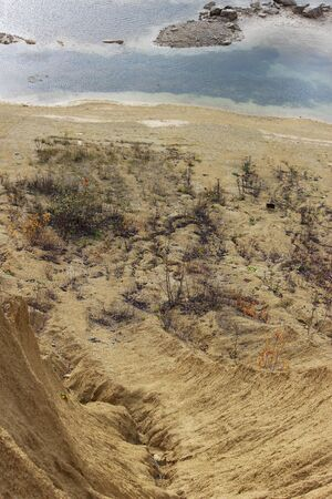 sand quarry. The crack between the two sand dunes is washed out by the rain and an artificial lake nearby.