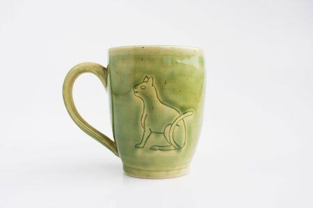 mug with the image of the hieroglyph Cat. Author's ceramics. Color Celadon. egyptian symbolism Standard-Bild - 142794631