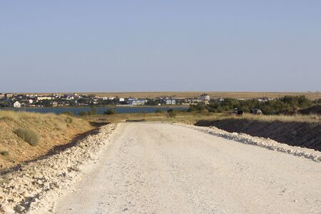 road under construction. Gravel poured in the steppe as a substrate in front of asphalt. Standard-Bild - 142794685