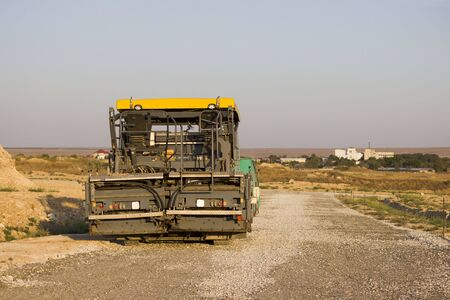 gravel and asphalt tamping machine stands on the road. road under construction. Gravel poured and tamped in the steppe as a substrate in front of asphalt.